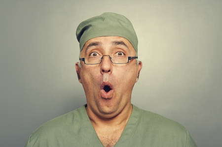 surprised man: portrait of amazed doctor over grey background