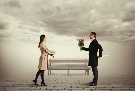 meanness: happy woman waiting man with flowers and knife