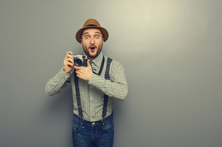 amazed young man with camera over grey background photo