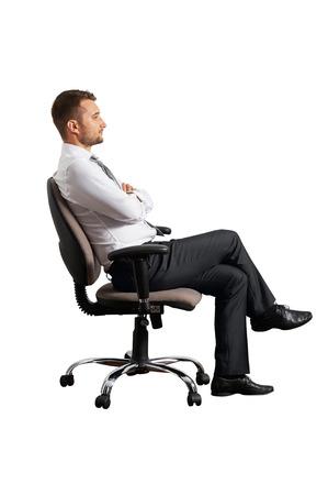 persona sentada: lateral de hombre de negocios en la silla de oficina. aislado en fondo blanco Foto de archivo