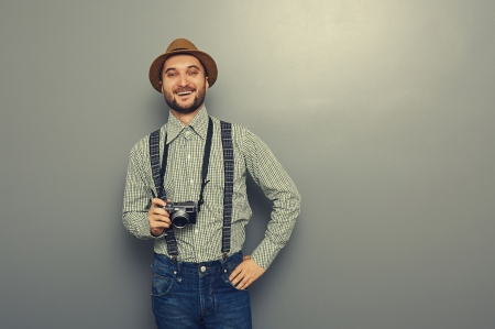 laughing hipster man holding retro camera over grey background photo