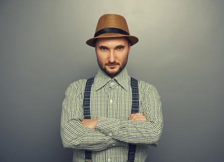 chapeau de paille: portrait d'homme sérieux de hippie en chapeau de paille et chemise à carreaux sur fond gris