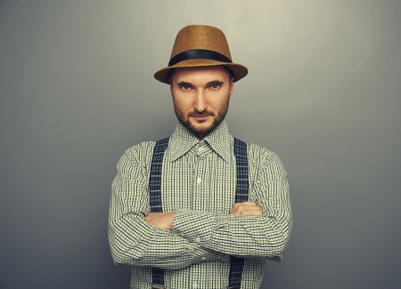 portrait of serious hipster man in straw hat and checked shirt over grey background photo