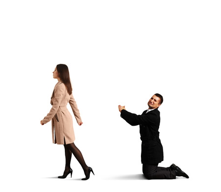 parting: sad man bending the knee before outgoing woman. isolated on white background