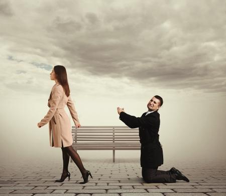 pareja enojada: hombre triste doblando la rodilla delante de la mujer que sale en al aire libre
