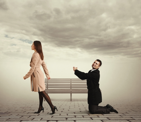 parting: sad man bending the knee before outgoing woman at outdoor