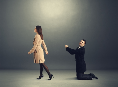 supplication: sad man bending the knee before outgoing woman in dark room