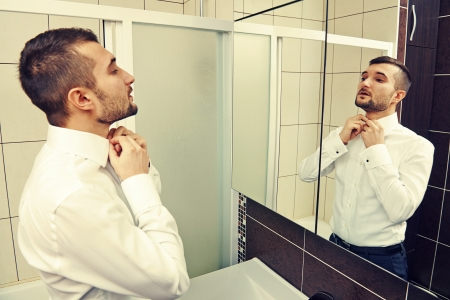 get dressed: handsome man looking at mirror and get dressed