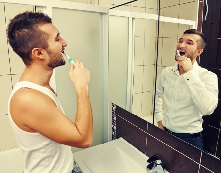 drowsy man brushing teeth and looking at successful businessman in the mirror photo