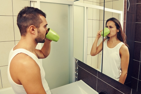 double game: sad man drinking tea and looking at a woman in the mirror Stock Photo