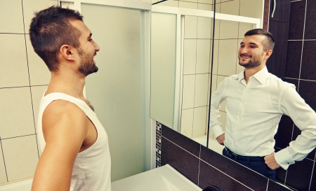 bathroom mirror: young man looking at successful himself Stock Photo