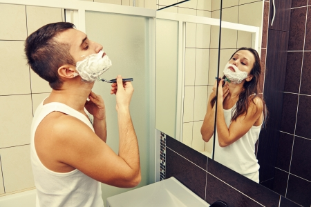 double game: young man shaving and looking at a woman in the mirror