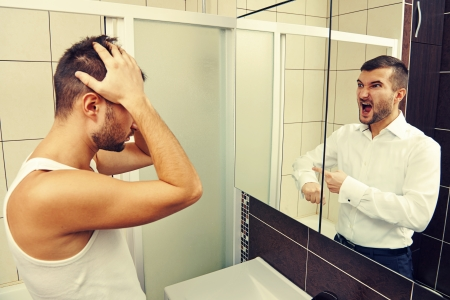 double game: sleepy man looking in the mirror at his angry reflection Stock Photo