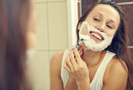 shaver: smiley woman looking at mirror and shaving her face  Stock Photo