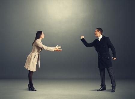zdradę: zły człowiek w sprzeczności z młodą kobietą. zdjęcia w ciemnym studio