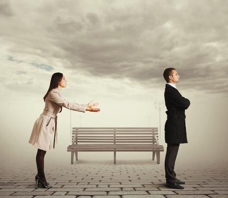 arrepentimiento: mujer joven pidiendo disculpas al hombre al aire libre