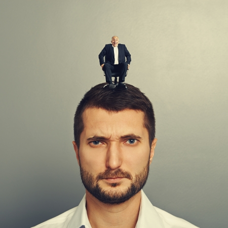 sponger: portrait of sad man with small man on the head