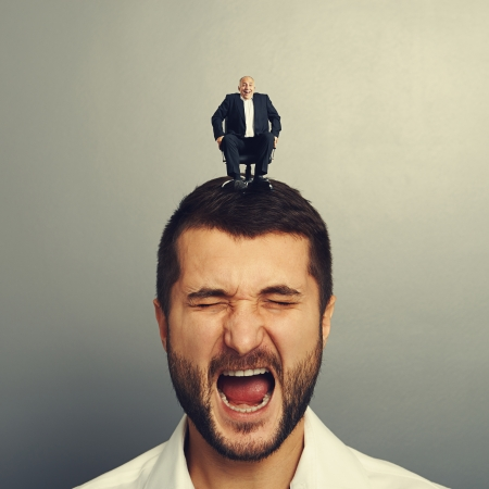 human voice: portrait of shocked man with small happy boss on the head