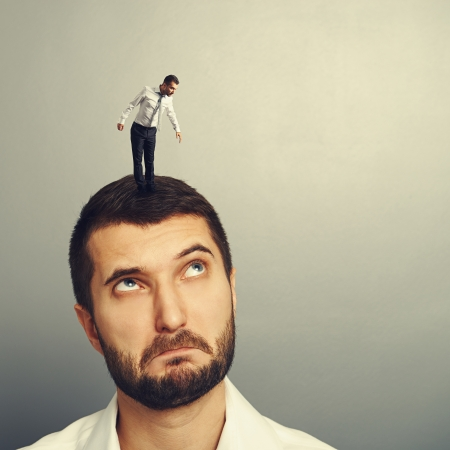 discredit: amazed man looking up at small man on the head