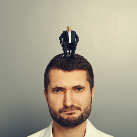sponger: portrait of displeased man with small boss on the head Stock Photo