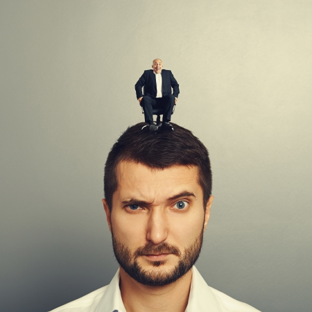 discredit: portrait of dissatisfied man with small man on the head