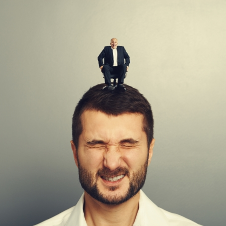 portrait of emotional man with small happy boss on the head Stock Photo