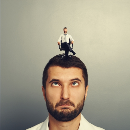sponger: portrait of foolish man with small smiley man on the head Stock Photo