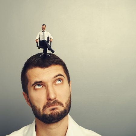 sponger: surprised man looking up at small successful man on the head