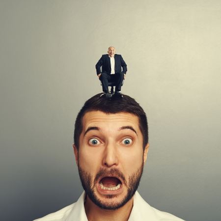 screaming scared man with laughing boss on the head