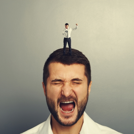 discredit: small angry boss standing on the head and screaming at worker over grey background Stock Photo