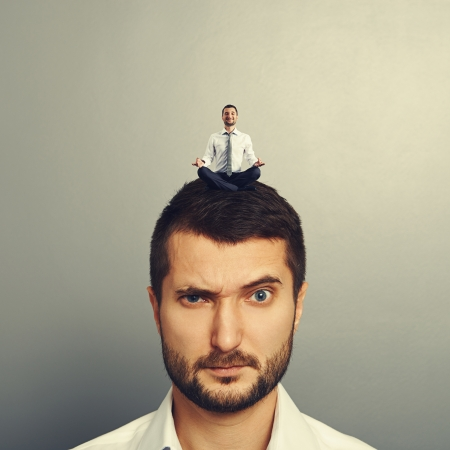 sponger: small happy man sitting on the head big dissatisfied man Stock Photo