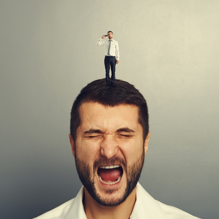 discontented: small man with gun holding on the head of stressed man