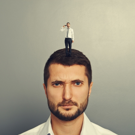 sponger: sullen man with small man on the head over grey background Stock Photo