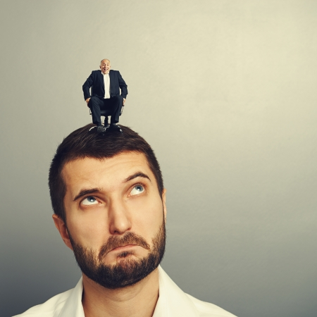 discredit: surprised man looking up at small man on the head