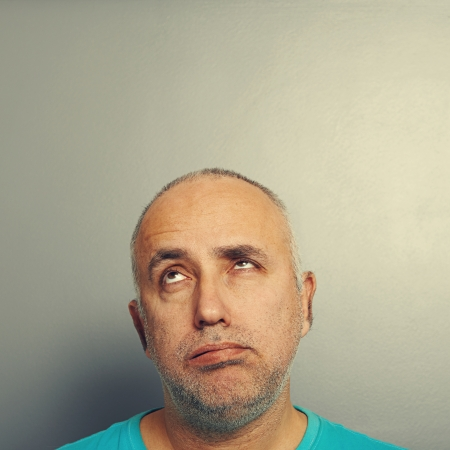 listless: portrait of bored senior man looking up over grey
