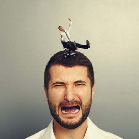 discredit: portrait of sad screaming man with small happy man on the head Stock Photo