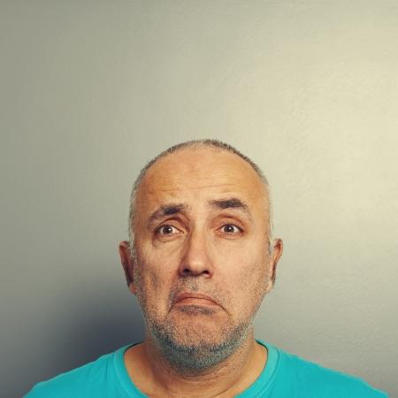 sorrowful: portrait of sorrowful senior man over grey