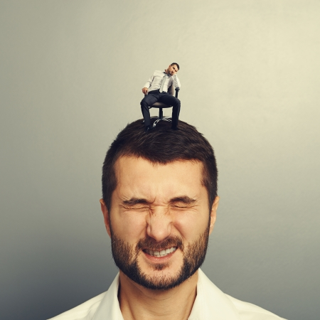 sponger: bored small man sitting on the head of another man Stock Photo