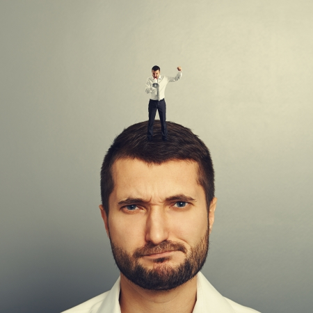 small boss standing on the head and screaming at bad worker Stock Photo