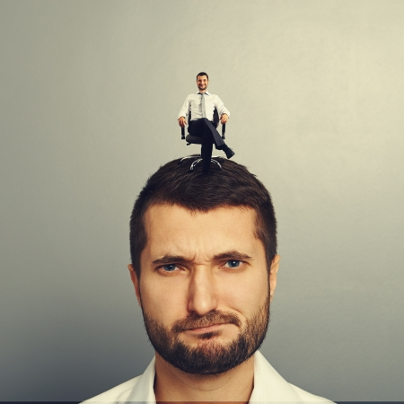 discontented: portrait of discontented man with happy successful man on the head