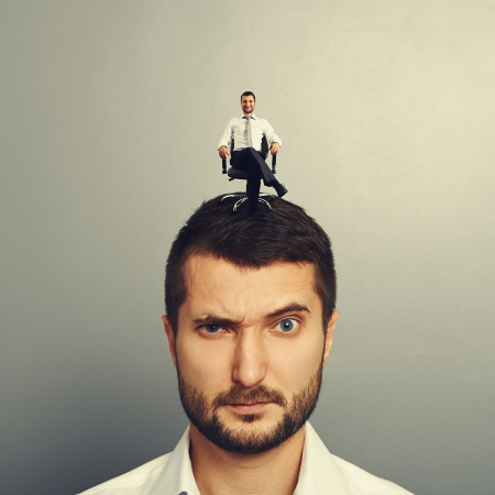 sponger: portrait of displeased man with small happy man on the head Stock Photo
