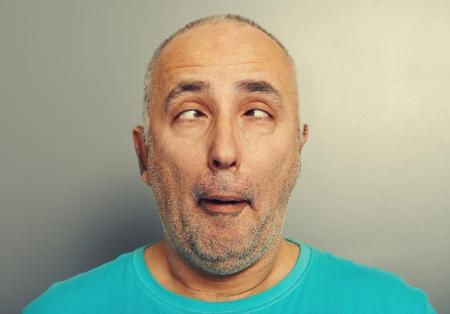 portrait d'un homme supérieur drôle de T-shirt bleu sur fond gris