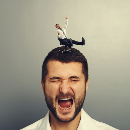 sponger: portrait of displeased screaming man with small happy man on the head Stock Photo