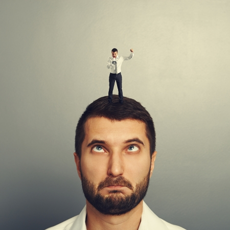 small boss standing on the head and screaming at foolish worker Stock Photo