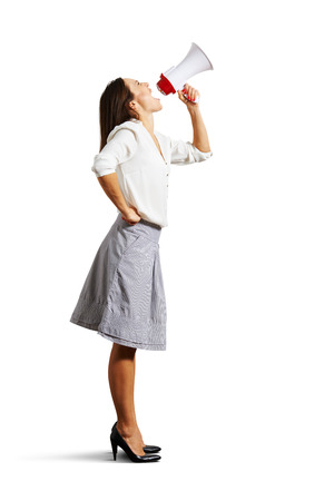 young woman looking up and shouting in megaphone. isolated on white  Stock Photo - 25201233