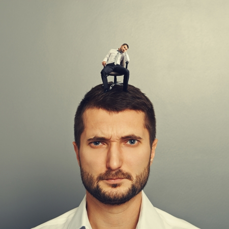 discredit: bored man sitting on the big head over grey background