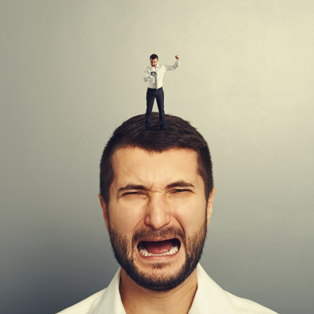 discredit: small angry boss standing on the head and screaming at worker