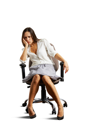 crestfallen: Mujer cabizbaja sentada en la silla. aislado en fondo blanco