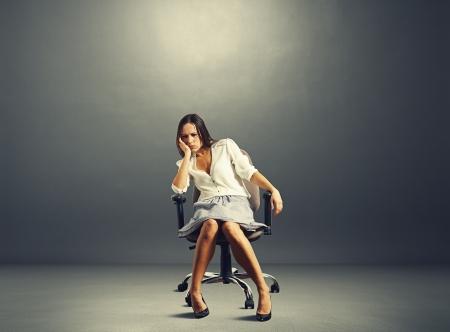 alicaído: Empresaria triste que se sienta en la silla en sitio vacío oscuro