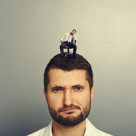 sponger: portrait of dissatisfied man with small bored man on the head